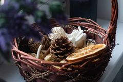 Basket with decorative elements on the windowsill. In the basket of dried flowers, orange, citrus, spices. In a black. Vase bottle are flowers of lavender stock photos