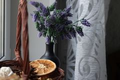 Basket with decorative elements on the windowsill. In the basket of dried flowers, orange, citrus, spices. In a black. Vase bottle are flowers of lavender royalty free stock images