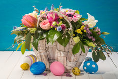 Basket with decorative flowers and colorful Easter eggs Royalty Free Stock Photo