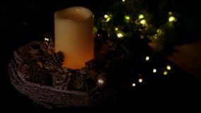 Basket with decorative items and a burning candle in the middle turning to blur stock footage
