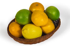 Basket with different tropical fruits isolated on white Stock Photo