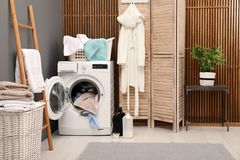 Basket with dirty towels on washing machine. In modern laundry room stock image