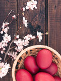 Basket with easter cake and red eggs on rustic wooden table. Top Stock Photo