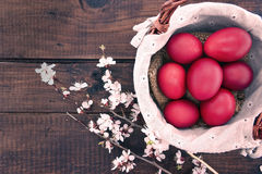 Basket with easter cake and red eggs on rustic wooden table. Top Royalty Free Stock Photo