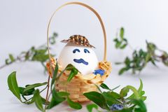 Basket with Easter egg with a mustache in a hat and green grass branch on white pastel background. Creative idea. Art food concept stock images