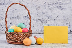 Basket with easter eggs. Blank yellow paper. Holiday of Christ Royalty Free Stock Images