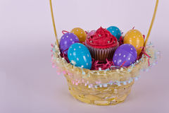 Basket with Easter eggs and cupcake Stock Photo