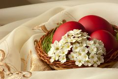 Basket with easter eggs and flowers. Easter decoration with red eggs,spring flowers and silk Royalty Free Stock Photos