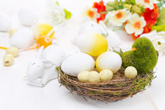Basket with easter eggs, flowers and rabbits Stock Photos