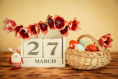 Basket of Easter eggs and flowers on wood table Stock Image