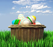 Basket with Easter eggs in the grass. Basket with colorful painted Easter eggs in the grass Stock Photo