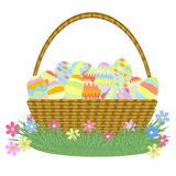Basket with Easter eggs on grass with flowers. Wicker basket with handle is filled with Easter eggs on grass with flowers on a white background Royalty Free Stock Image
