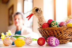 Basket with Easter eggs and hen in senior woman house Royalty Free Stock Image
