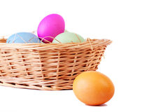 Basket with easter eggs and one on foreground Royalty Free Stock Photos
