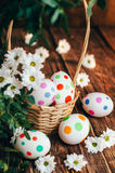 Basket with Easter eggs painted in a circle, spring branch with green leaves,. Wooden orange - brown background Royalty Free Stock Photography