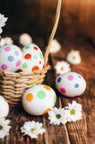 Basket with Easter eggs painted in a circle, spring branch with green leaves, Stock Photo