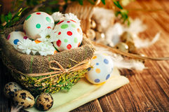 Basket with Easter eggs painted in a circle, spring branch with green leaves,. Wooden orange - brown background Royalty Free Stock Photos