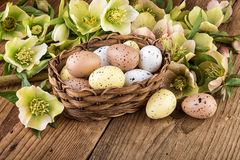 Basket with Easter eggs in pastel color on wooden background Royalty Free Stock Image