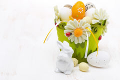 Basket with easter eggs and rabbits on white wooden table Royalty Free Stock Images