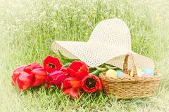 Basket with Easter eggs, red tulips, hat Royalty Free Stock Photo