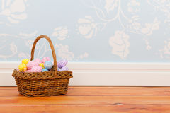 Basket easter eggs in room with blue vintage wall paper Royalty Free Stock Image