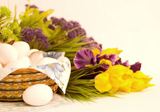 Basket with Easter eggs and spring flowers Stock Photo