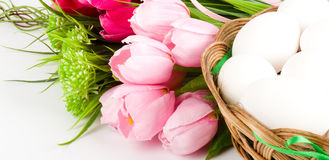 Basket with Easter eggs and spring tulips stock photo