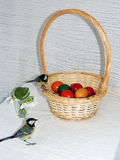 Basket with Easter Eggs and Titmice. Basket with colorful Easter eggs, snowdrops  and two titmice Royalty Free Stock Photo