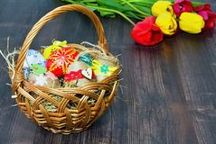 Basket with Easter eggs and tulip background. Basket with colored eggs and the Easter tulip background on a wooden board Stock Photo