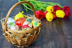 Basket with Easter eggs and tulip background. Basket with colored eggs and the Easter tulip background on a wooden board Stock Images