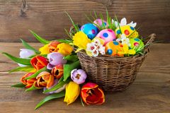 Basket with Easter eggs and tulips. Royalty Free Stock Photography
