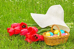 Basket with Easter eggs, tulips and hat Stock Photography