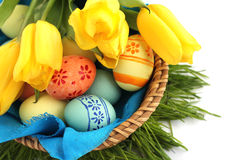 Basket of easter eggs and tulips on white. Basket of colored easter eggs and tulips on white background Stock Photos