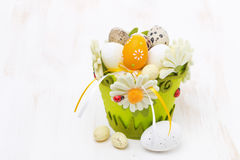 Basket with easter eggs on white wooden table Royalty Free Stock Photo