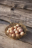Basket with eggs. Basket with organic eggs on a weathered wooden bench at farm Royalty Free Stock Photography