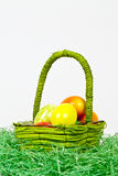 Basket with eggs. Some Colorful eggs in a green basket Stock Photography