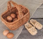 Rustic still life with basket with eggs and bast shoes Stock Image