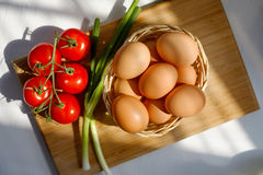 Basket of Eggs with a Bunch of Tomatoes Royalty Free Stock Photos