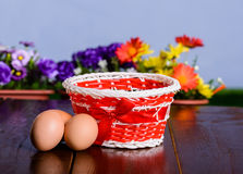Basket with eggs on rustic wooden table. Royalty Free Stock Image