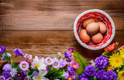 Basket with eggs on wooden table. Background. Copy spase left. Stock Photos