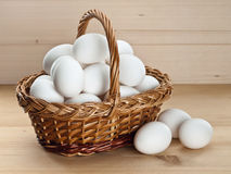 Basket with eggs on a wooden table Royalty Free Stock Photo