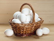 Basket with eggs on a wooden table Royalty Free Stock Photos
