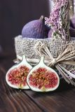 Basket of fig fruits with the halves one on a table. Stock Images