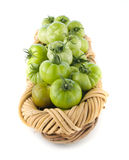 Basket filled with green tomatoes Stock Photos