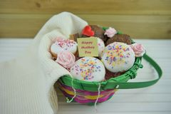 Happy mothers day words on a note in a gift basket of homemade cakes. A basket filled with homemade and baked little vanilla and chocolate cakes or cupcakes with Royalty Free Stock Image