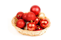 Basket filled with red and golden christmas balls. Isolated on white royalty free stock photo