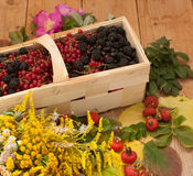 A basket filled with ripe berries and a bouquet of filed flowers on a wooden surface decorated with hips and autumn leaves Royalty Free Stock Images