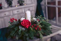 Basket with fir branches, a candle and roses on a wooden table. Basket with fir branches, candles and flowers on a wooden table Stock Photo
