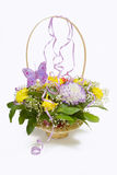 Basket of flowers. With a butterfly and ribbons Stock Photo