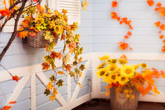 Basket with flowers and autumn leaves hanging on the blue wall o. F wooden building Royalty Free Stock Photos